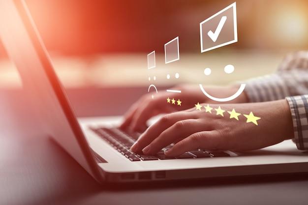 사업가 키보드 노트북에 스마일을 누르면입니다. 고객 서비스 평가 개념입니다.