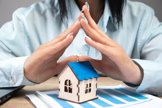 사업가는 그녀의 손으로 집을 보호합니다