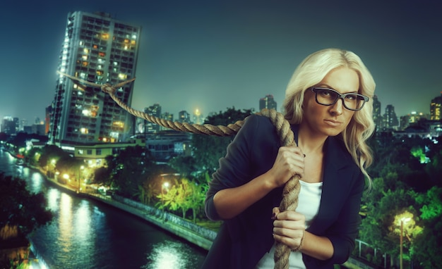 Businesswoman pulling a big building with a rope in a big night city