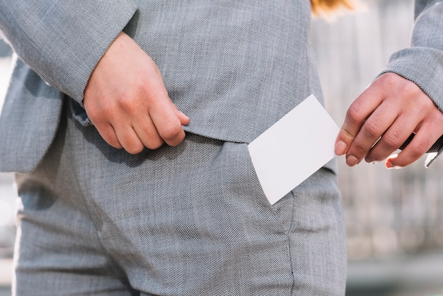Businesswoman pulling out business card outdoors