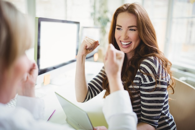 Businesswoman punching in air while discussing with colleague in creative office