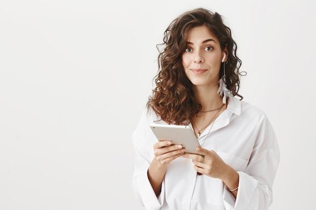 Imprenditrice mettere auricolari wireless e tenere tavoletta digitale, sorridendo