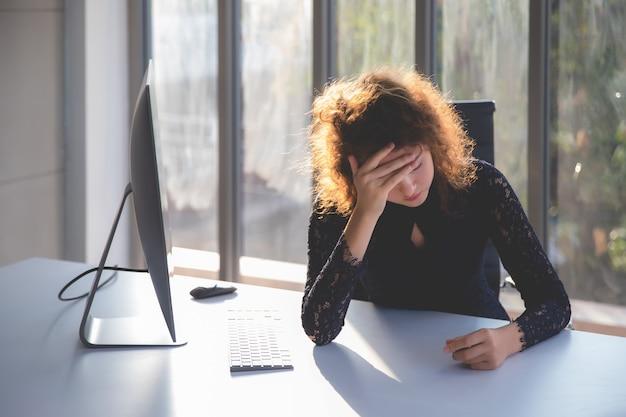 Предприниматель кладет руки на лоб и имеет грустное лицо. на столе в ее офисе установлен компьютер.