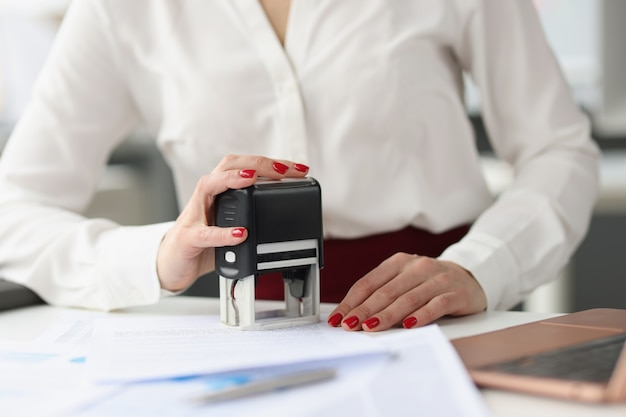 Businesswoman puts stamp on credit documents at work desk. small and medium business development concept