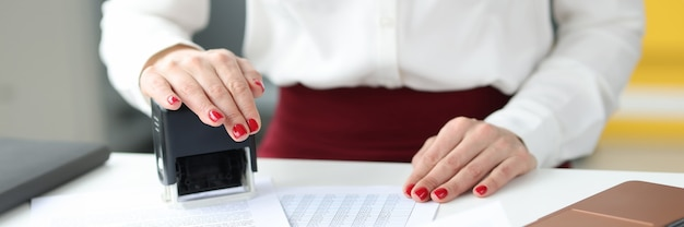 Businesswoman puts a stamp on documents on work table services of notaries and notary offices