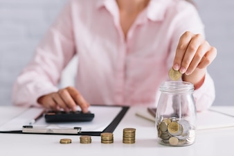 Businesswoman putting coins in jar using calculator at workplace