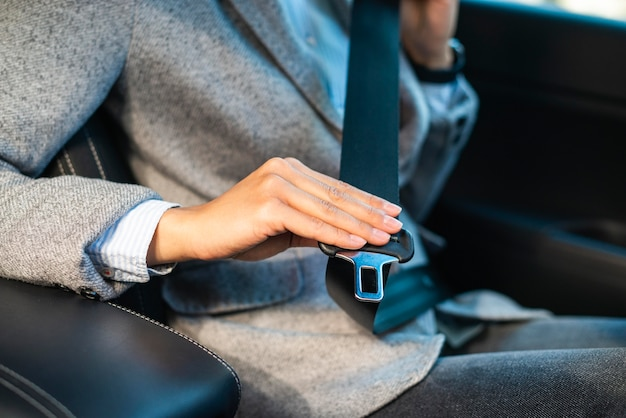 Businesswoman putting on the seat belt in the car