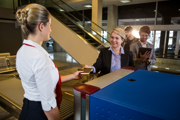 Businesswoman in queue receiving passport and boarding pass