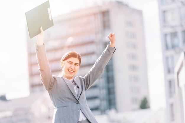Businesswoman raising arms outdoors
