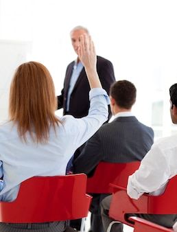 Businesswoman raising her hand up at a conference