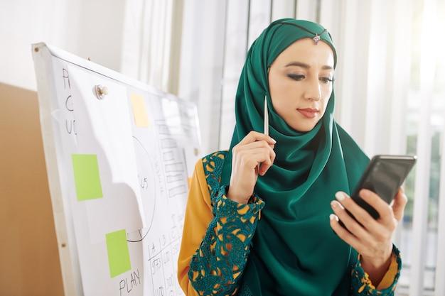 Деловая женщина читает статью на смартфоне