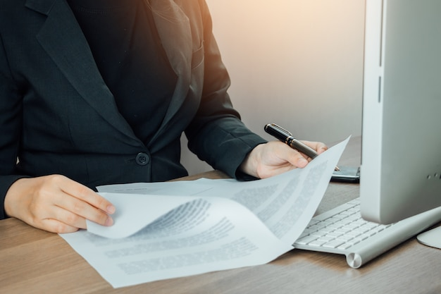 Businesswoman reading and checking terms and conditions document on her desk