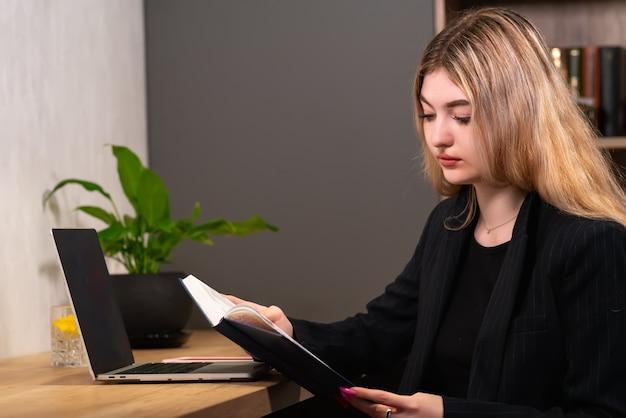 Деловая женщина читает из журнала за своим столом в офисе, проверяя свое расписание на день, крупным планом
