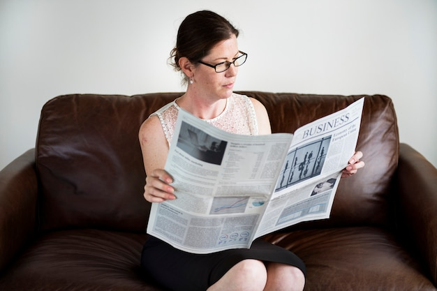 Businesswoman reading a newspaper on a couch