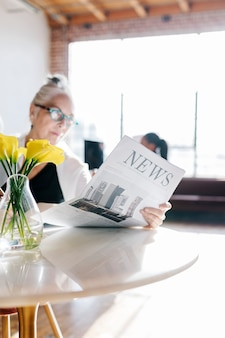 Деловая женщина читает газету в мастерской