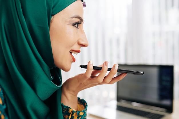 Businesswoman recording voice message