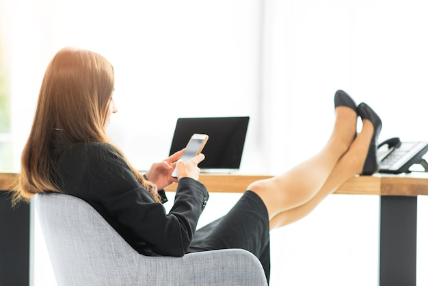 Businesswoman relaxing at desk using smartphone in the office