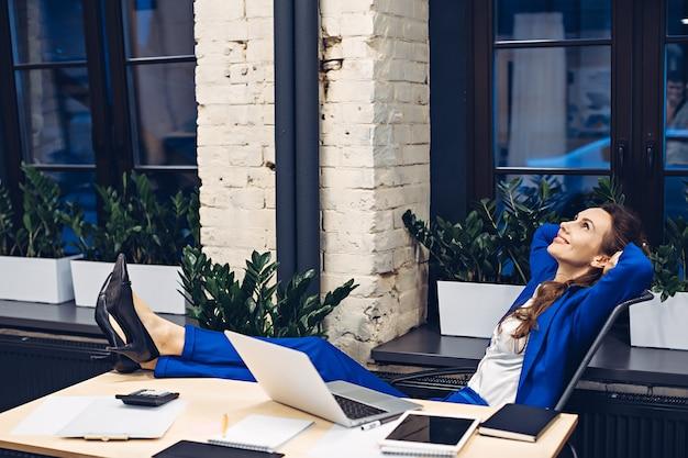 オフィスの椅子でくつろぐビジネスウーマン