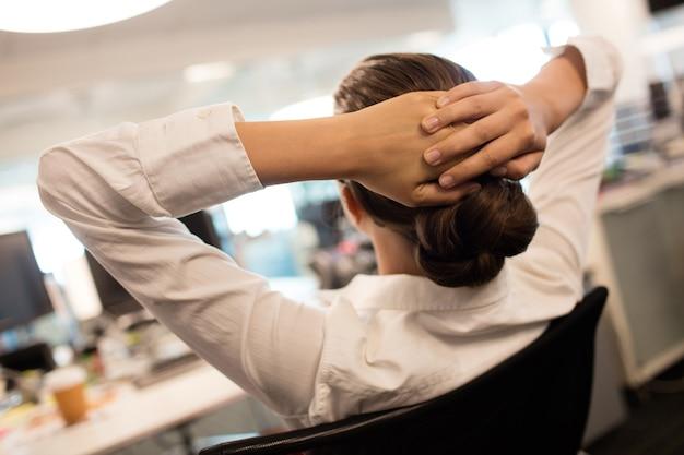 Деловая женщина, расслабляющаяся на стуле в офисе