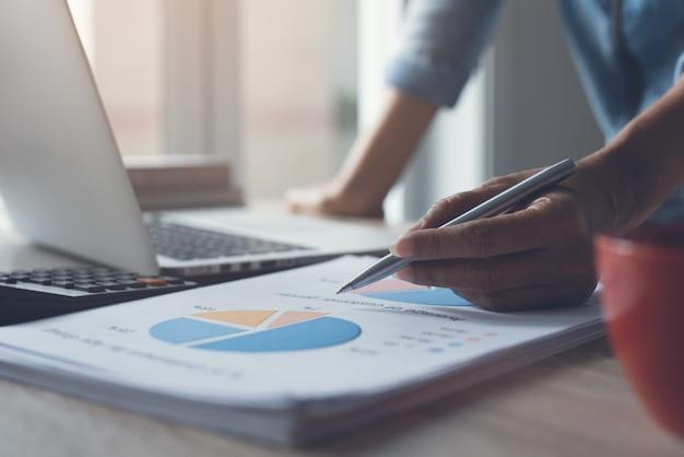 Коммерсантка рассматривая бизнес-отчет пока работающ в офисе