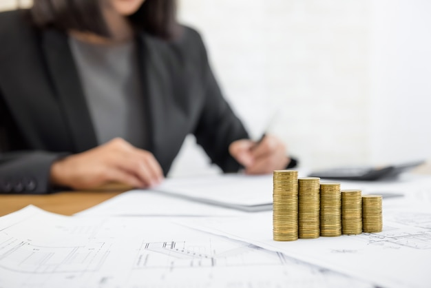 Businesswoman reviewing document with money and blueprints on the table
