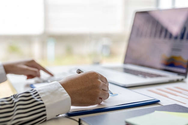 기업 재무 정보 시트의 막대 차트를 가리키는 펜을 들고 있는 사업가의 손은 재무 부서에서 제공하는 재무 정보를 조사합니다.