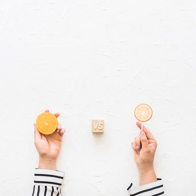 Businesswoman's hand holding citrus slice versus lollipop over white background