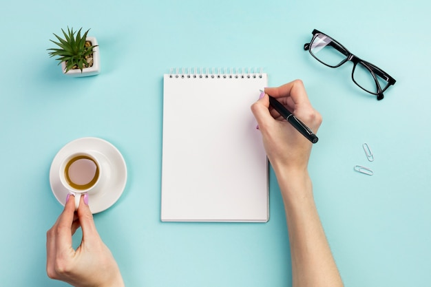 Businesswoman's hand writing on notepad with pen and holding coffee cup over the office desk Premium Photo