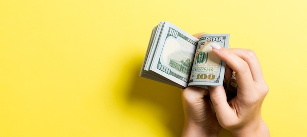Businesswoman's hands counting one hundred dollar bills on colorful surface.  copy space. top view
