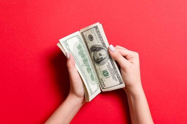 화려한 배경에서 100달러 지폐를 세는 사업가의 손. 급여 및 임금 개념입니다. 투자 개념의 상위 뷰입니다.