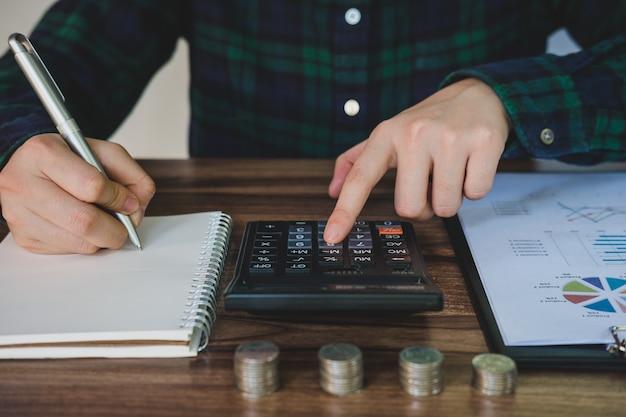 사업가 돈을 절약 하 고 책상에 금융 계정을 분석합니다.
