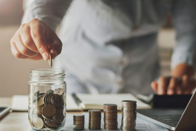 Businesswoman saving money by hand puting coins in jug glass