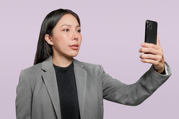 전화 보안 기술의 잠금을 해제하기 위해 그녀의 얼굴을 스캔하는 사업가