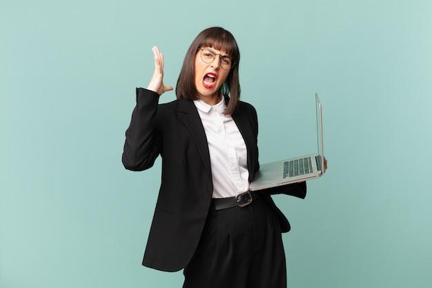 Деловая женщина кричит с поднятыми руками, чувствуя ярость, разочарование, стресс и расстройство