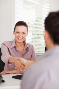 Businesswoman shakes hands with a man