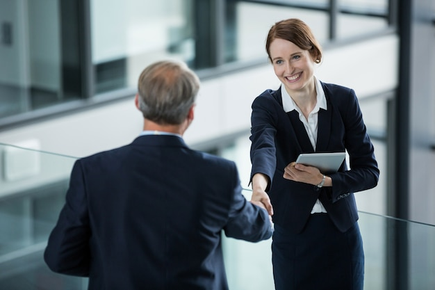 Businesswoman shaking hands with her colleague
