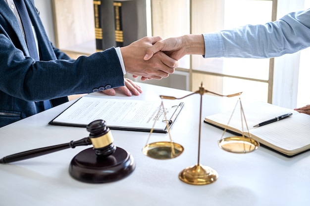 Businesswoman shaking hands with male lawyer after discussing good deal of contract in courtroom