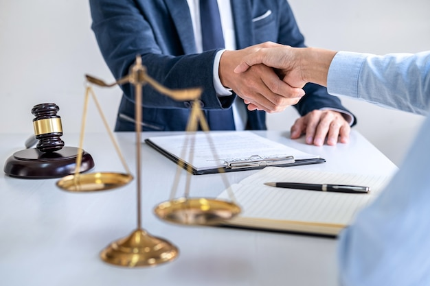 Деловая женщина, пожимая руку юристу-мужчине после обсуждения значительного контракта в зале суда