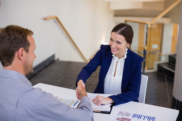 Businesswoman shaking hands with man at desk