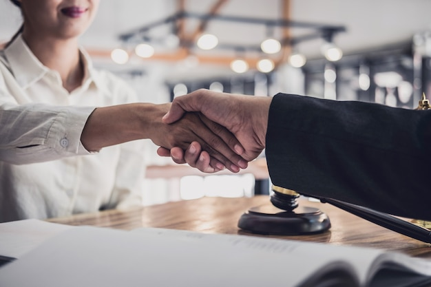 Businesswoman shaking hands with professional male lawyer after discussing good deal of contract in courtroom