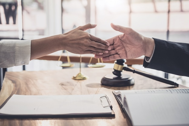 Businesswoman shaking hands with professional male lawyer after discussing good deal of contract