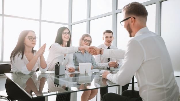 空いているポジションの候補者と握手する実業家。成功するビジネスキャスティングの概念