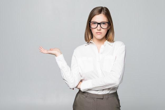 Businesswoman showing copy space for product with open hand palm. smiling friendly expression on young businesswoman wearing glasses isolated on white wall.