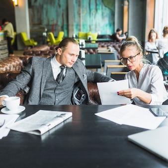 レストランで彼女のパートナーに文書を見せるビジネスマン