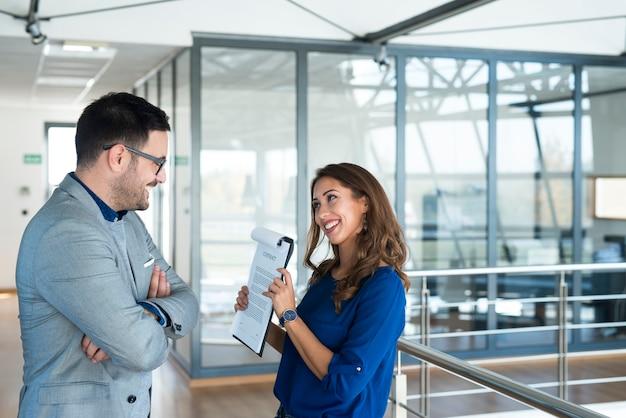 Деловая женщина показывает документы менеджеру по маркетингу в офисе компании