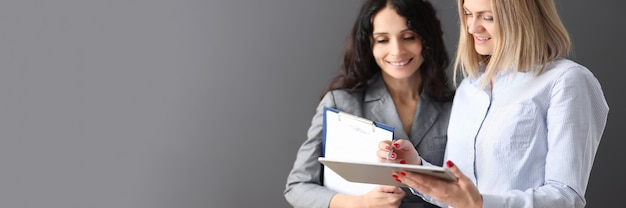 Деловая женщина показывает информацию коллеге на планшете и улыбается деловому партнерству