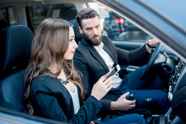 Businesswoman showing phone to the businessman sitting together on the front in the car