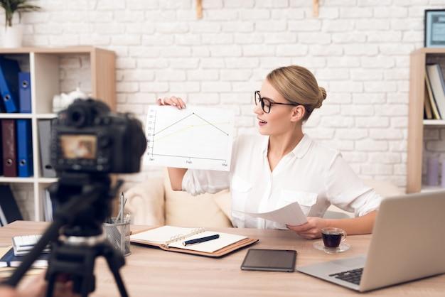 Предприниматель показывает графики на камеру.