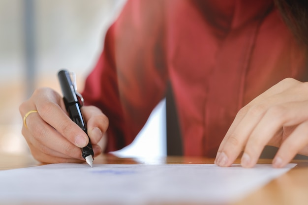 Businesswoman signing a contract document making a deal.