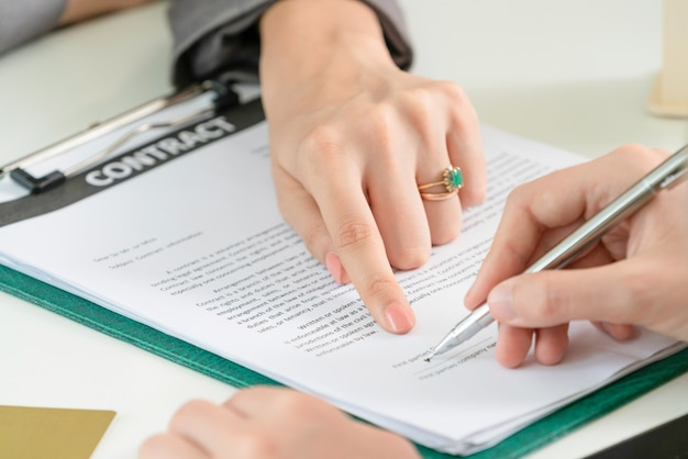 Businesswoman signs agreement contract in office.